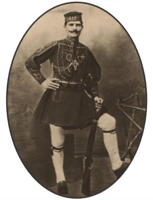 Ολόσωμη αναμνηστική φωτογραφία τού Γεωργίου Δικώνυμου - Μακρή, από την Καλλικράτη Χανίων. Ο καπετάνιος φέρει αραβίδα Μάνλιχερ Μ 1903. Στην πρωτότυπη φωτογραφία, στην πάνω αριστερή γωνία φέρει τίτλο στα ελληνικά και γαλλικά 'Καπετάν Μακρής Μακεδών' και 'Capitain Makris Macedonien'. Στην οπίσθια όψη, στην αριστερή πλευρά αναγράφεται καθέτως το όνομα τού εκδότη: 'Εκδόται - Π. Κοσμετάτος & Σία. - Αθήναι'.