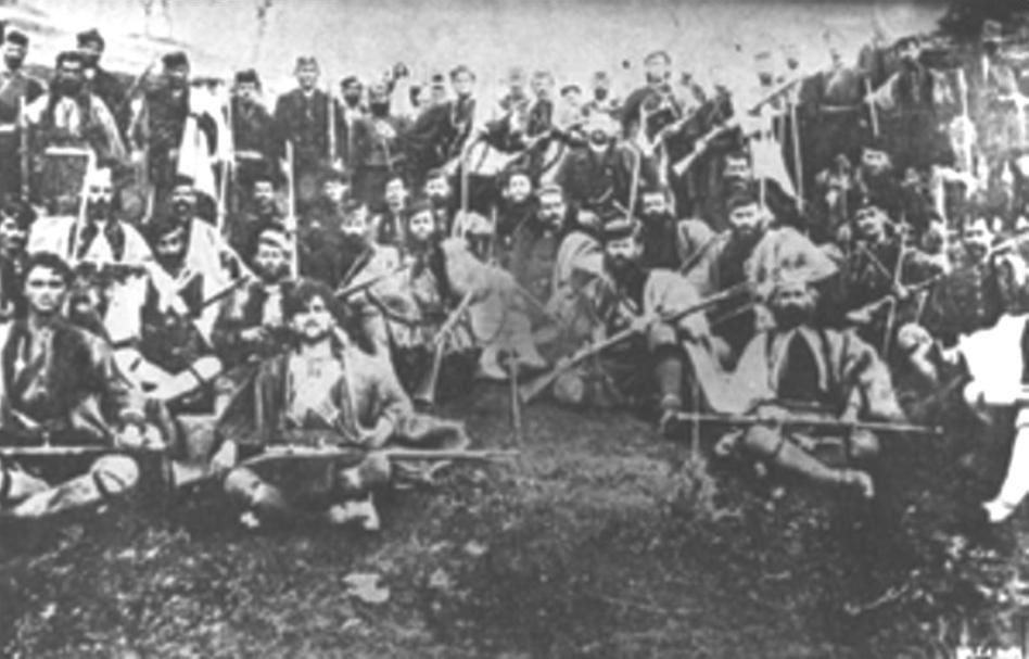 Ο Αντώνιος Βλαχάκης με τους άντρες τού ένοπλου σώματός του. Διακρίνεται καθισμένος στο κέντρο τής φωτογραφίας, σε πρώτο πλάνο. Ακριβώς αριστερά του εικονίζεται ο Λουκάς Κόκκινος με την φουστανέλα.