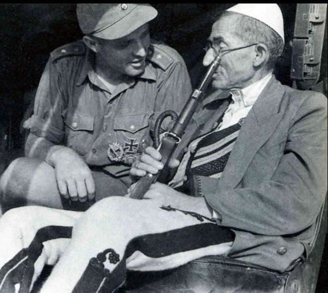German soldier of the Wehrmacht talking to an Albanian.